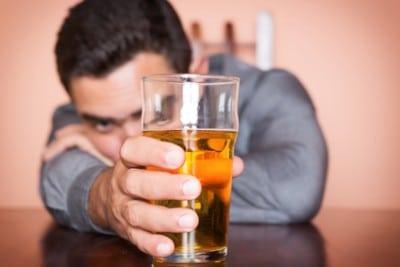 Betrunkener Mann der ein Glas Bier hält